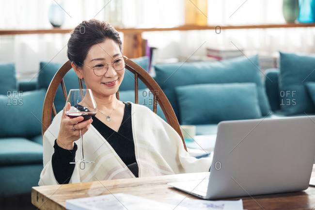 Elegant middle-aged drinking wine and watching a movie on her laptop