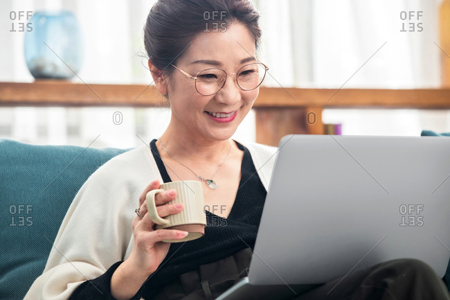 Middle-aged lady using her laptop while sitting on the sofa