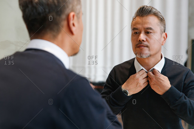 Middle-aged man getting dressed and looking in mirror