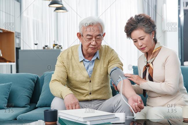 Elderly woman measures her husband's blood pressure