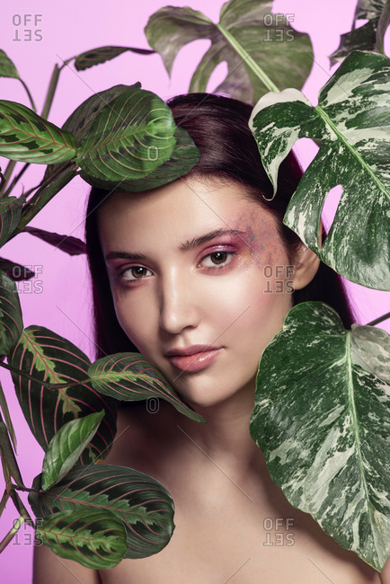 Portrait of a young woman with leafy plants in front of pink background