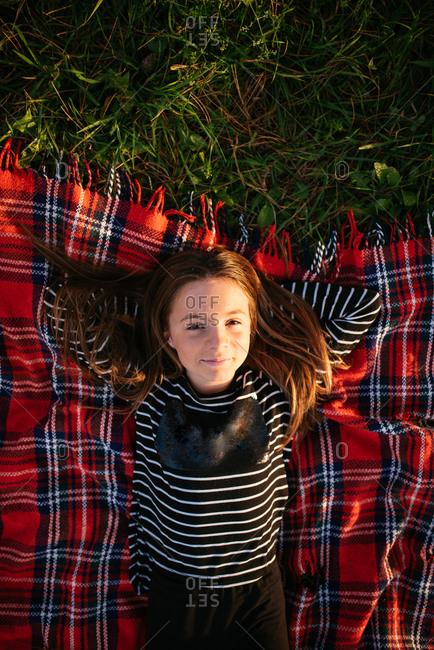 Overhead view of young girl lying in grass on a red plaid blanket