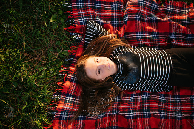 Top view of young girl lying in grass on a red plaid blanket