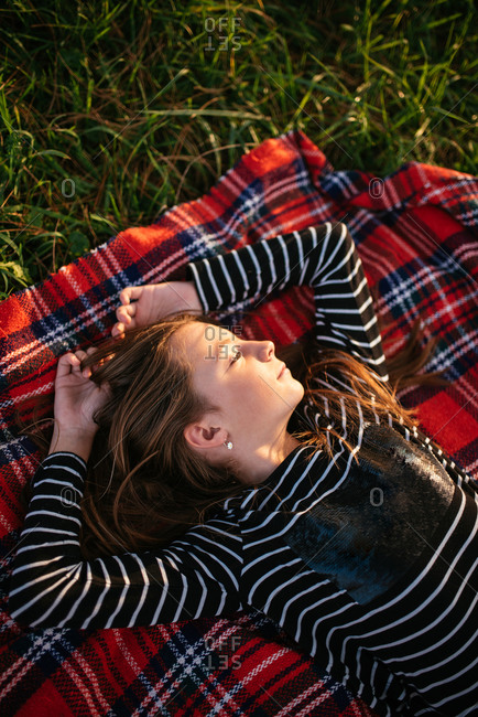 Overhead view of young girl lying in grass looking away