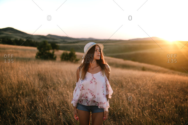 Woman walking through a field of tall grass during sundown