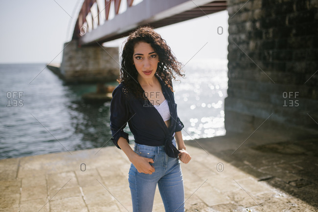 Portrait of a young woman with curly hair standing on a pier