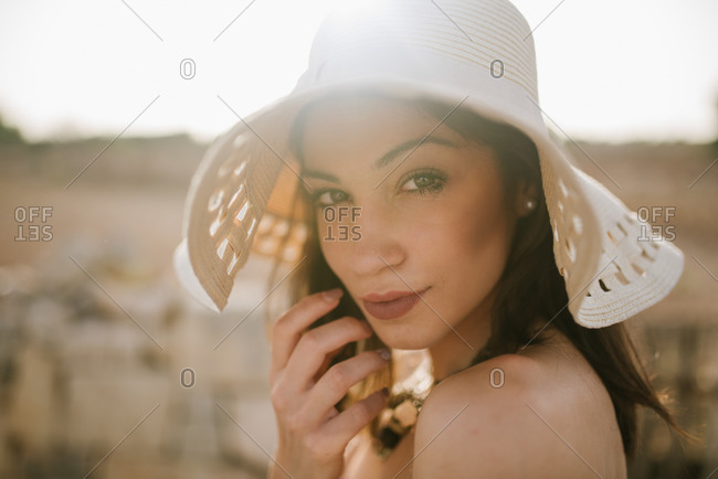 Portrait of beautiful young woman wearing hat in the sunshine