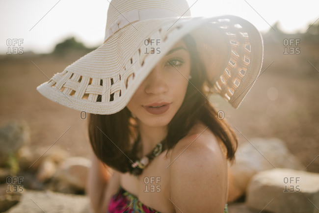 Portrait of beautiful young woman wearing hat that is partially covering her face