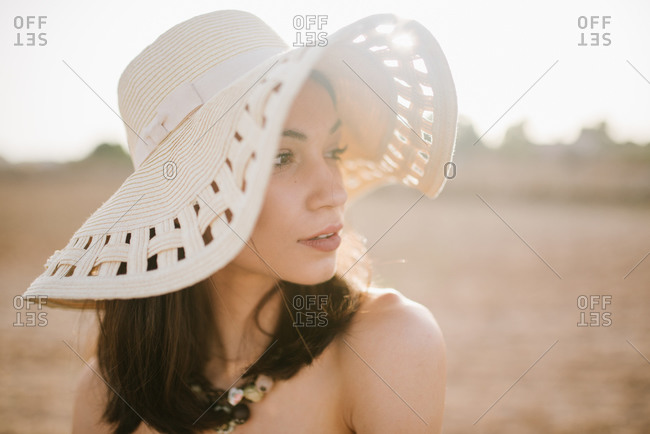 Portrait of beautiful young woman wearing sunhat and looking away