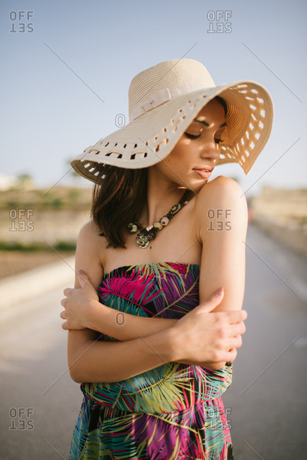 Portrait of beautiful young woman wearing a colorful dress and sunhat