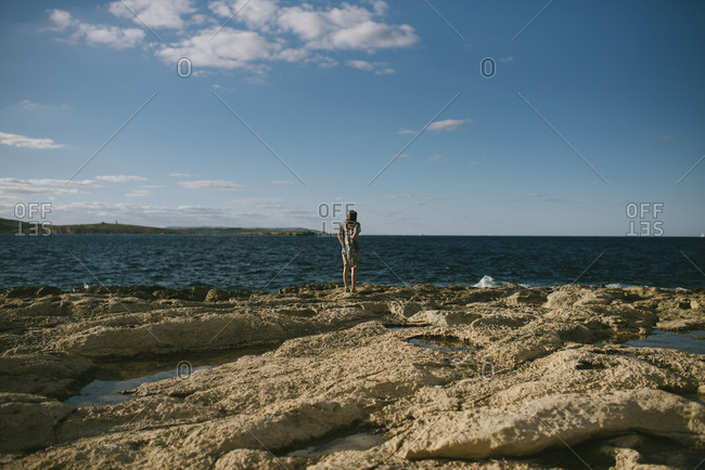 Young woman looking at the ocean on a rocky beach