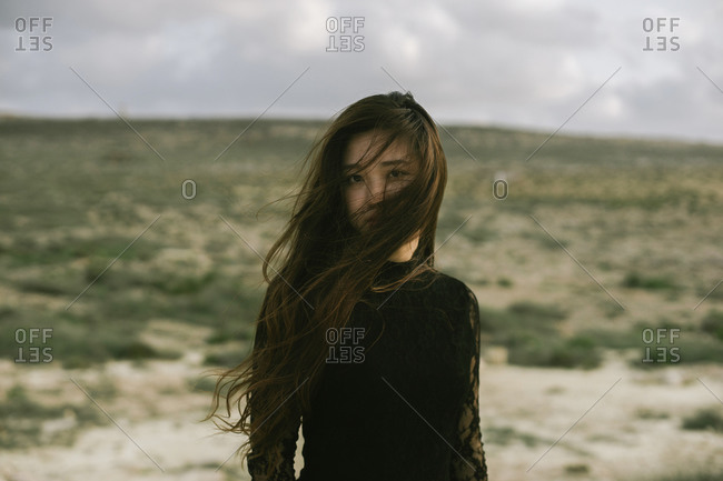 Young Asian woman at the beach with wind blowing her long hair in her face