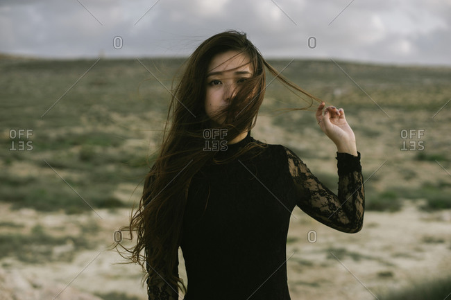 Young Asian woman at the beach pulling her wind blown long hair from her face