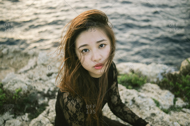 Young Asian woman sitting on rocky beach looking at camera