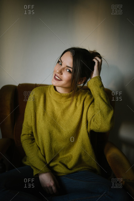 Young brunette woman sitting in armchair scratching her head and looking at camera