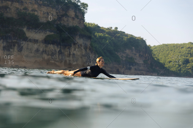 Female surfer lying on surfboard, Kuta, Lombok, Indonesia