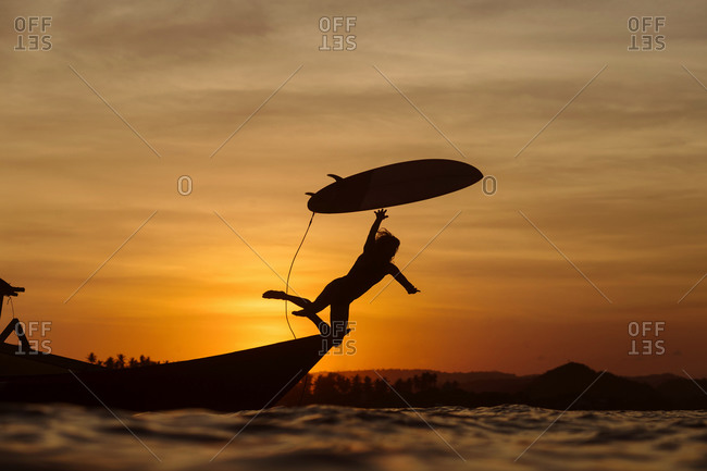 Surfer jumping into water, Gerupuk, Lombok, Indonesia