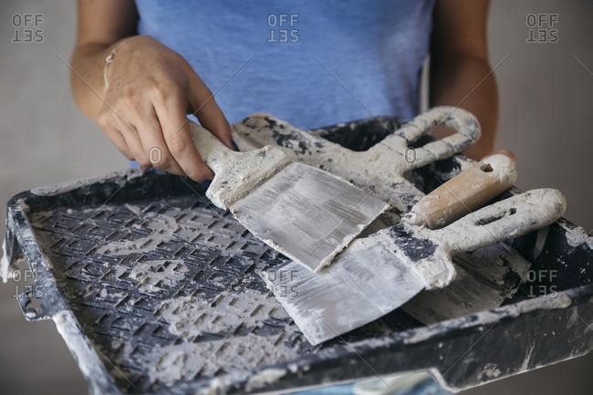 Woman with dirty brick trowels, Tikhvin, Leningrad Oblast, Russia