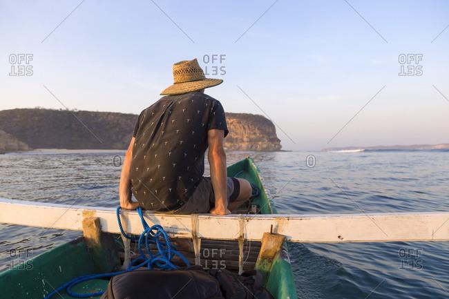 Man sitting in outrigger boat, Kuta, Lombok
