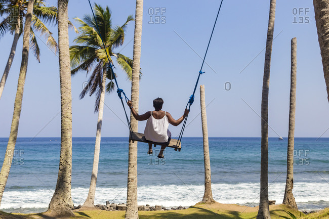 Woman on swing hanging from palm trees on seashore, Karangasem, Bali, Indonesia