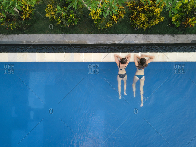 Two women in swimming pool in hotel, Balian, Bali, Indonesia