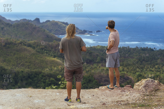 Two men standing on cliff and looking at view of seashore, Lombok, Indonesia