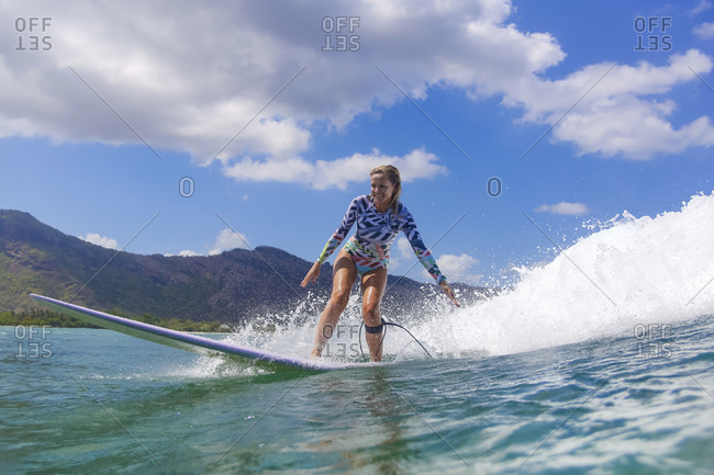 Female surfer riding wave near coast, Sumbawa, Indonesia