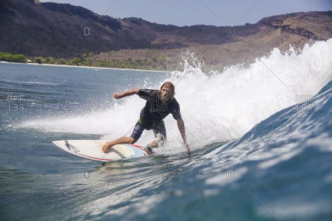 Male surfer riding wave near coast, Sumbawa, Indonesia