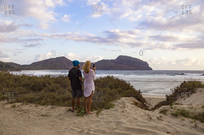 Couple photographing ocean coastline, Lombok, Indonesia