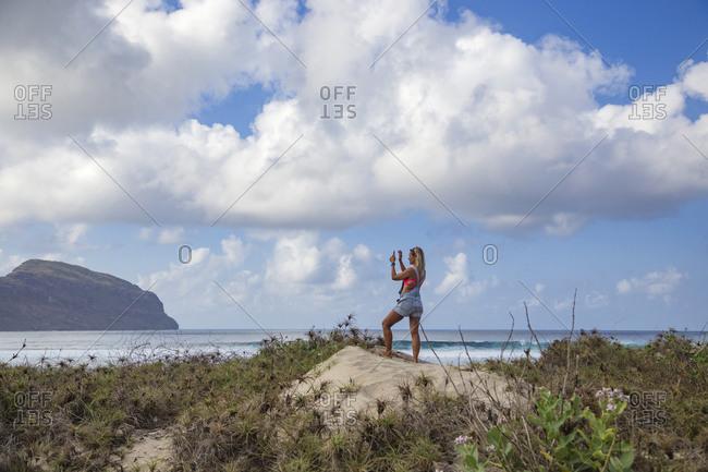Woman photographing ocean coastline, Lombok, Indonesia