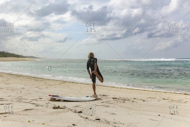 Man stretching on beach, Sumbawa, Indonesia