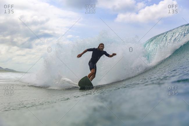 Surfer riding wave, Sumbawa, Indonesia
