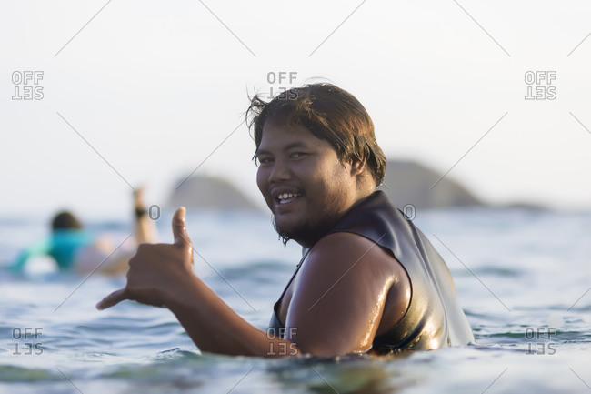 Asian man swimming in sea, Kuta, Lombok, Indonesia