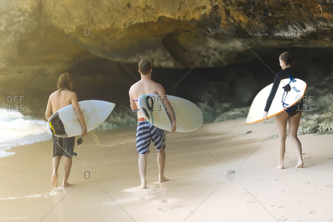 Three people with surfboards on beach, Uluwatu, Bali, Indonesia