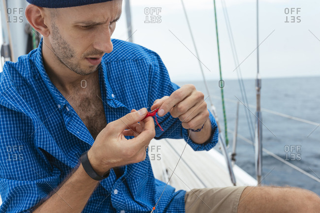 Man preparing for fishing on sailboat, Kuta, Lombok, Indonesia