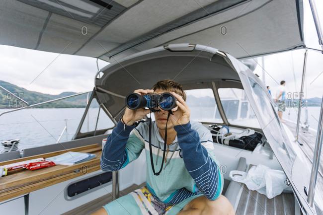 Man using binoculars on sailboat, Kuta, Lombok, Indonesia