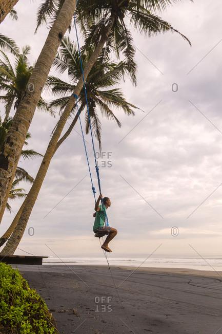 Man playing on swing, Bali, Indonesia