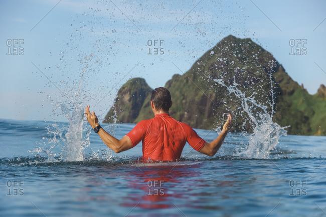 Man splashing in sea, Sumbawa, Indonesia