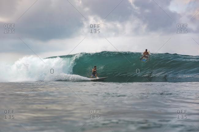 Surfers on wave, Sumbawa, Indonesia