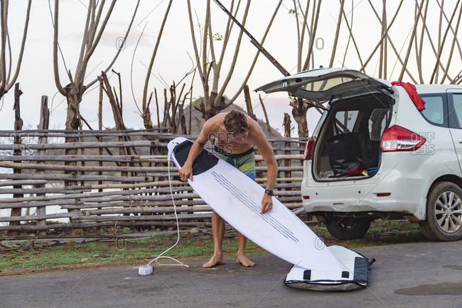 Surfer with surfboard near car, Sumbawa, Indonesia