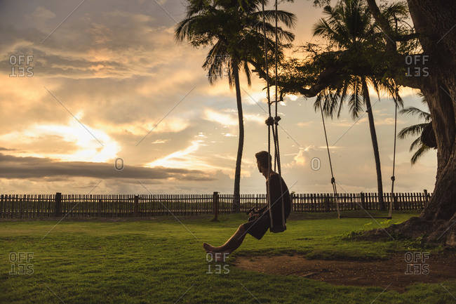 Man sitting on swing at sunset, Sumbawa, Indonesia