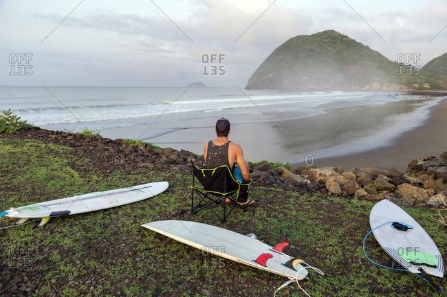 Man with surfboards sitting on seashore, Sumbawa, Indonesia
