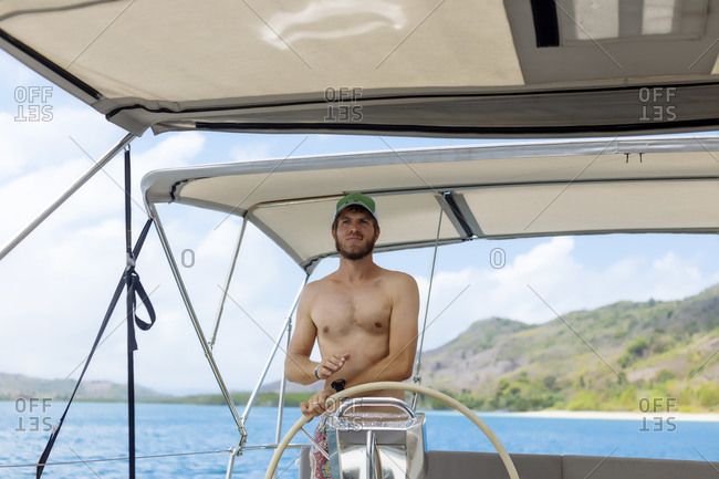 Man steering sailboat on water