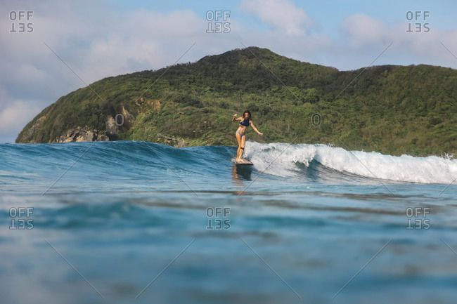 Female surfer riding a wave, Sumbawa, Indonesia