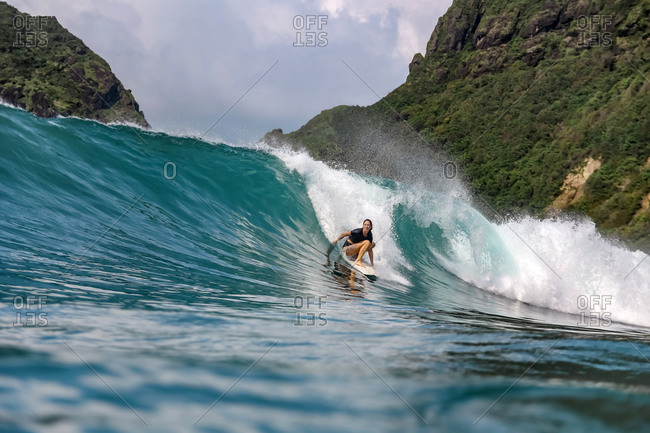 Female surfer riding a wave in Indonesia