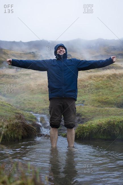 Man standing in hot spring, Reykjadalur, Iceland