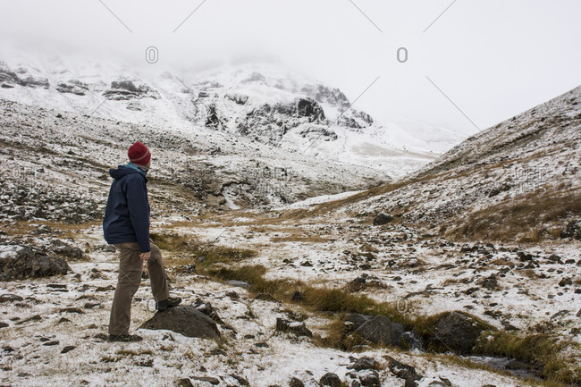 Young man looking at snowy mountain landscape at Mount Esja, Kjalarnes, Iceland
