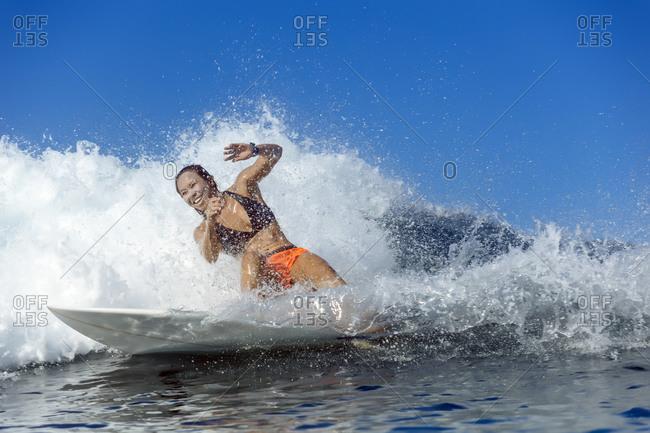 Woman surfing in sea, Banda Aceh, Sumatra, Indonesia