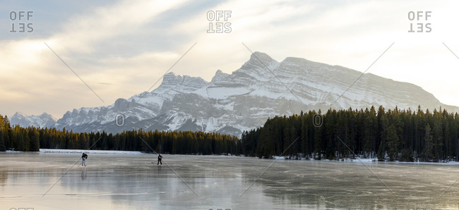 People ice skating on frozen Two Jack Lake, Alberta, Canada