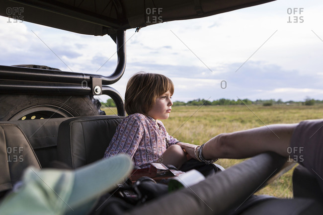 A five year old boy on safari, in a jeep in a game reserve